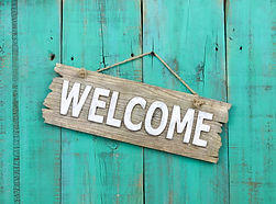 Rustic wood welcome sign hanging on weat