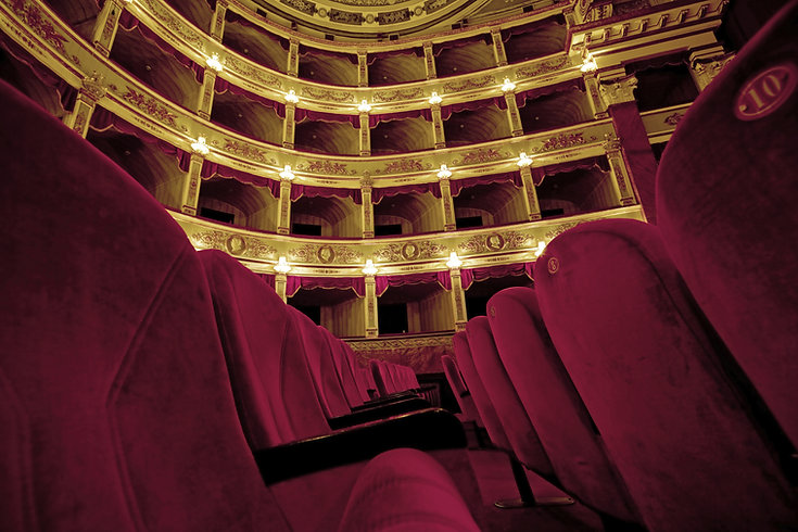 Beautiful old theatre with red velvet chairs and curtains, and gold accents.