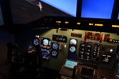 Image of an airplane cockpit in a flight simulator. Shows how Wise Insights DiSC Profile, Five Behaviors of a Cohesive Team, and Situational Improvisation workshops are a safe place for teams to practice high stakes communications.