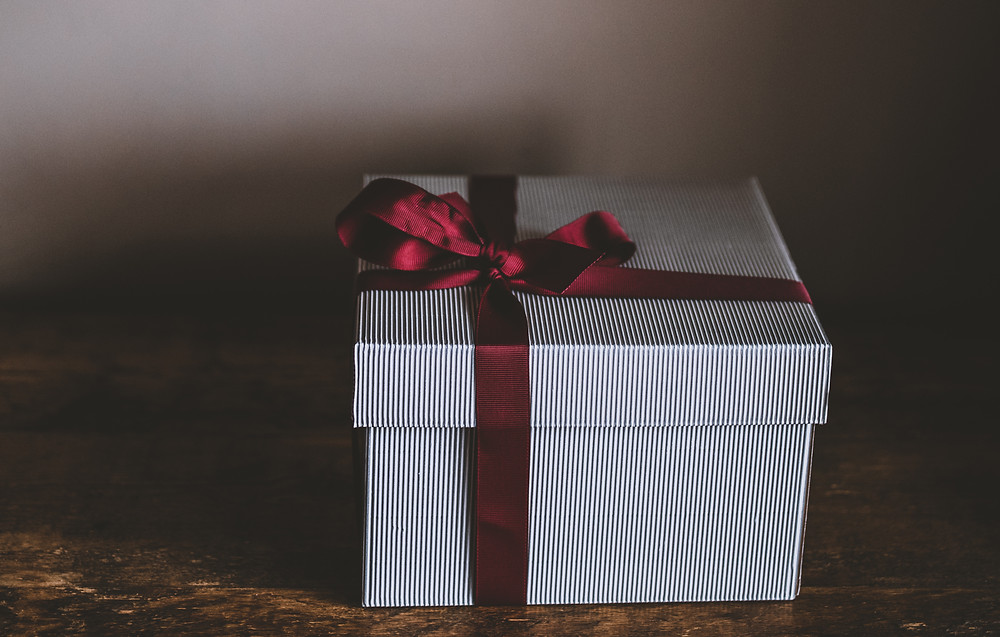 Picture of a grey and white striped box with a lid that's wrapped with a deep crimson bow in the corner representing a carefully wrapped gift of a business leader's presence.