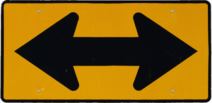 A yellow street sign with a double arrow going left and right signifying a two way street.