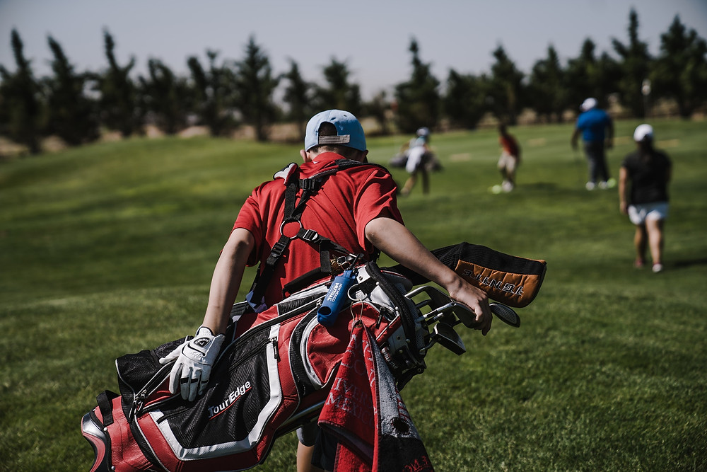 Photo of a caddy carrying a golf bag filled with clubs behind a group of golfers.