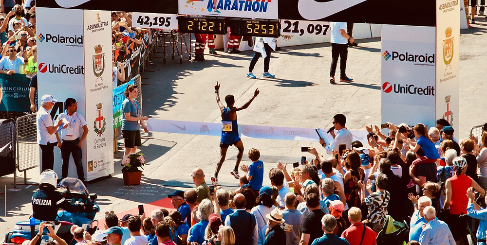 A picture of a runner winning the race at the finish line
