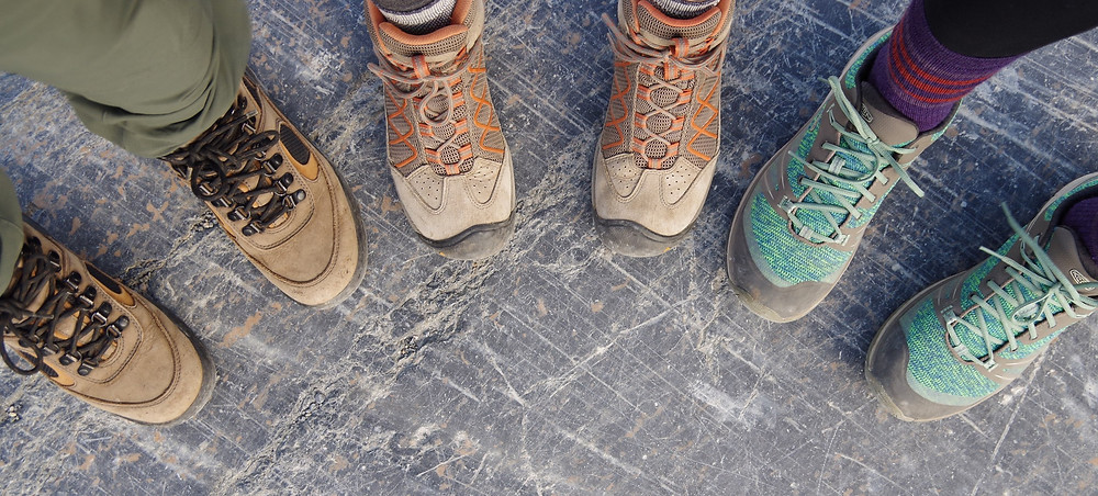 Close up picture of sets of feet, each wearing a different type and color hiking shoe.