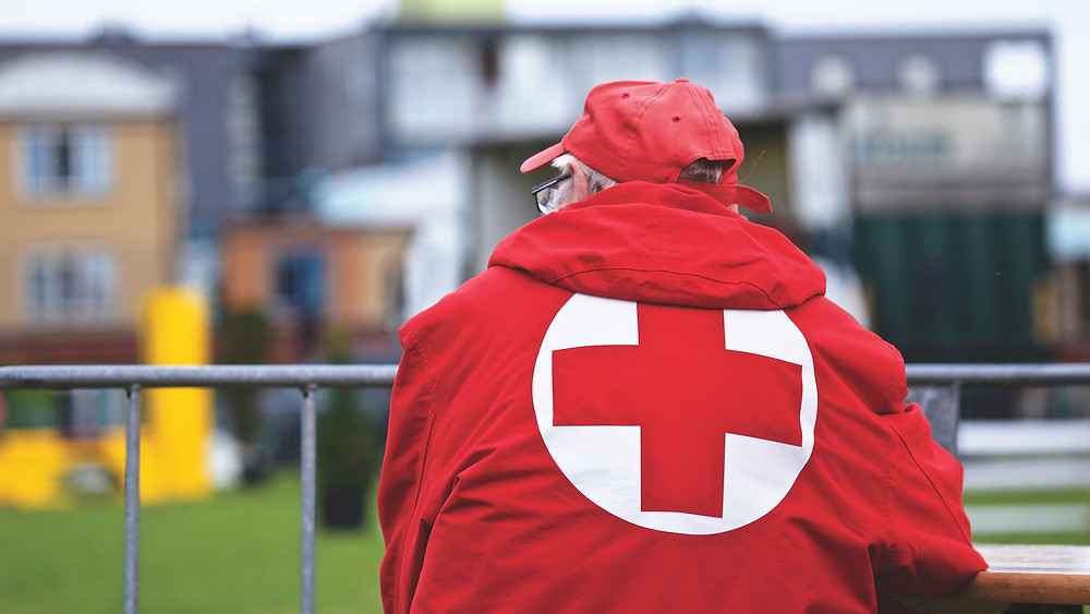 Picture of a man standing on a balcony overlooking a field and several buildings while wearing a warm jacket with a red cross logo on the back on an overcast day.