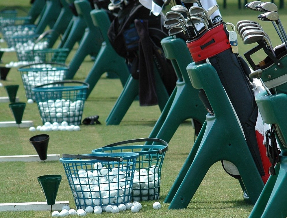 Picture of a row of golf bags, clubs, and baskets of range balls at the driving range. The image signifies the practice business owners need to do to improve their performance.
