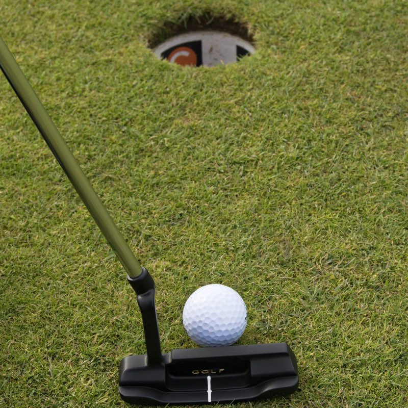 Photo of a golf ball on the green a few feet from the cup and a putter poised to tab the ball into the hole.