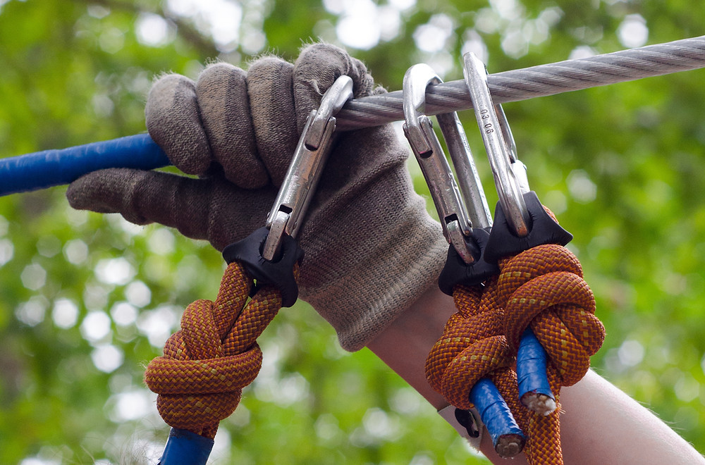 Image of a person's gloved hand grasping a metal cable while clipping in a third carabiner and rope for safety. Represents the safety that business owners get when they invest in the right tools like business coaching.