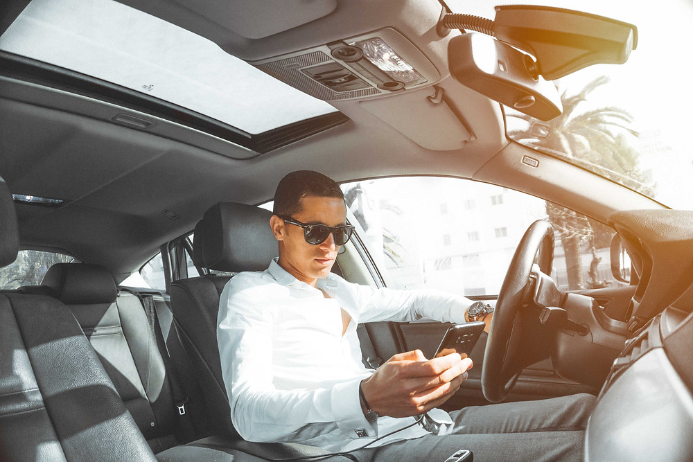 Photo of a man wearing sunglasses and looking down at the phone in his hand while sitting behind the steering wheel of a car.