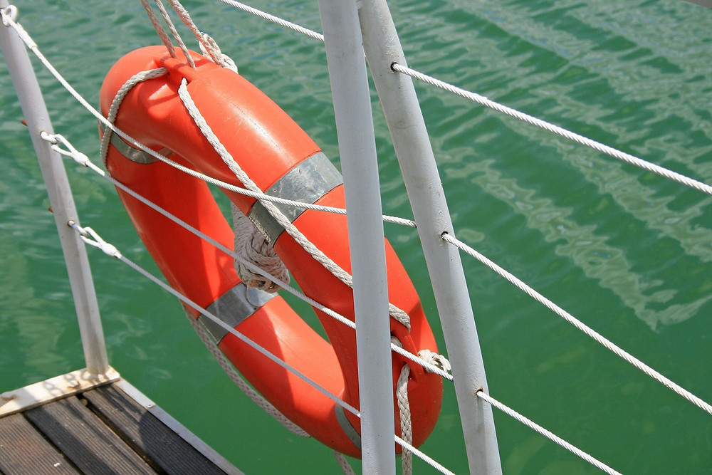 Photo of an orange life saving ring hanging on the rope railing of a ship in green ocean water suggesting there's a life saving aspect of coaching.