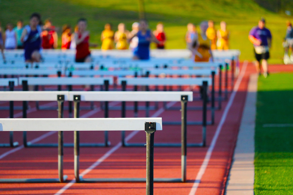 A photo of a long line of hurdles on a track. A pack of runners in the distance begins to race.