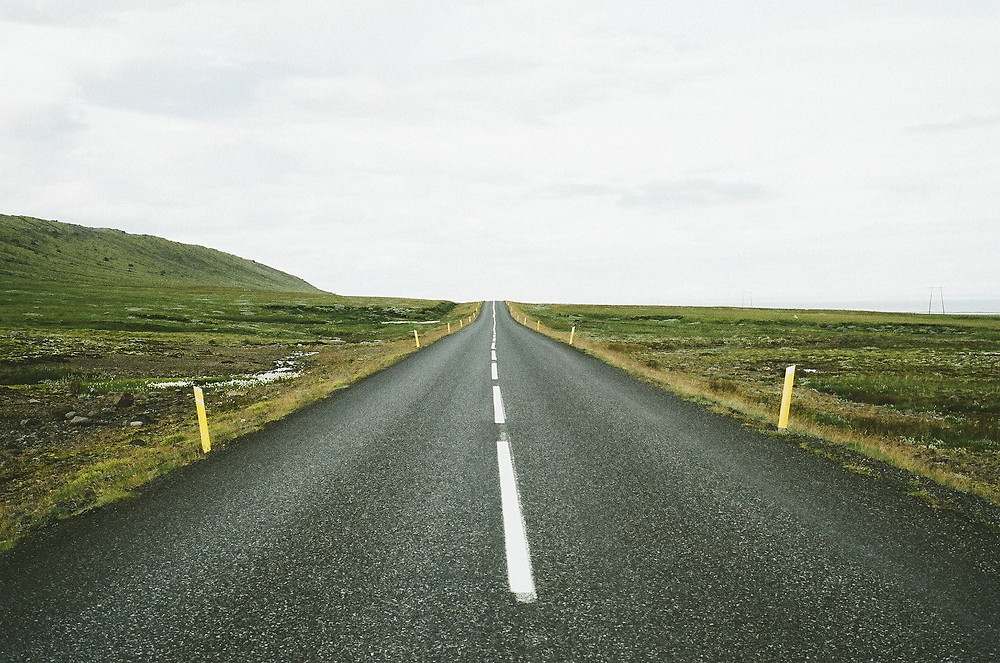 Picture of a straight, two-lane road with a dashed white center line and yellow markers on both sides signifying a defined path in a coaching program