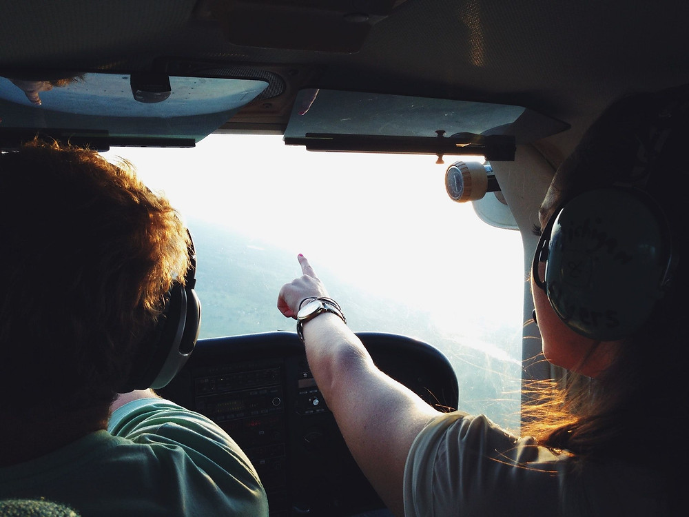 Photo of a woman wearing aircraft communications headphones and sitting in the copilot's seat pointing to an object on the horizon as if calling it to the pilots attention.
