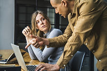 Image of two people in a tense coversation at a computer. Shows how Wise Insights helps teams prepare for high stakes conversations through engaging an iteractive workshops.