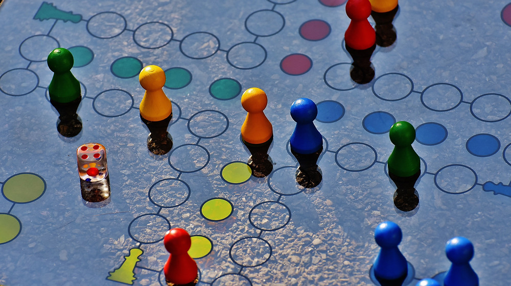 Picture of many different colored pawn shaped pieces on a board game with a single die cast on the number four.