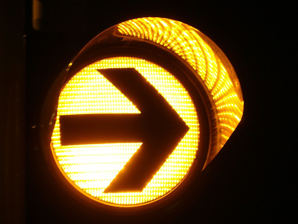 Photograph of a yellow stoplight at night with a bold, right-facing arrow in black over the glowing yellow lens signifying that caution can help business owners avoid failing in a pivot.