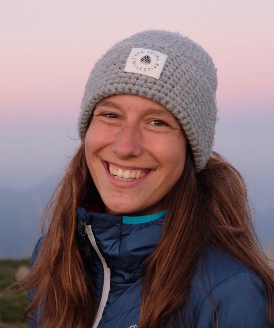 Porträt Jasmin Wunderli: Eine Mitte 20-jährige Frau, die strahlend lächelt. Sie trägt eine graue Mütze und hat langes, braunes Haar.