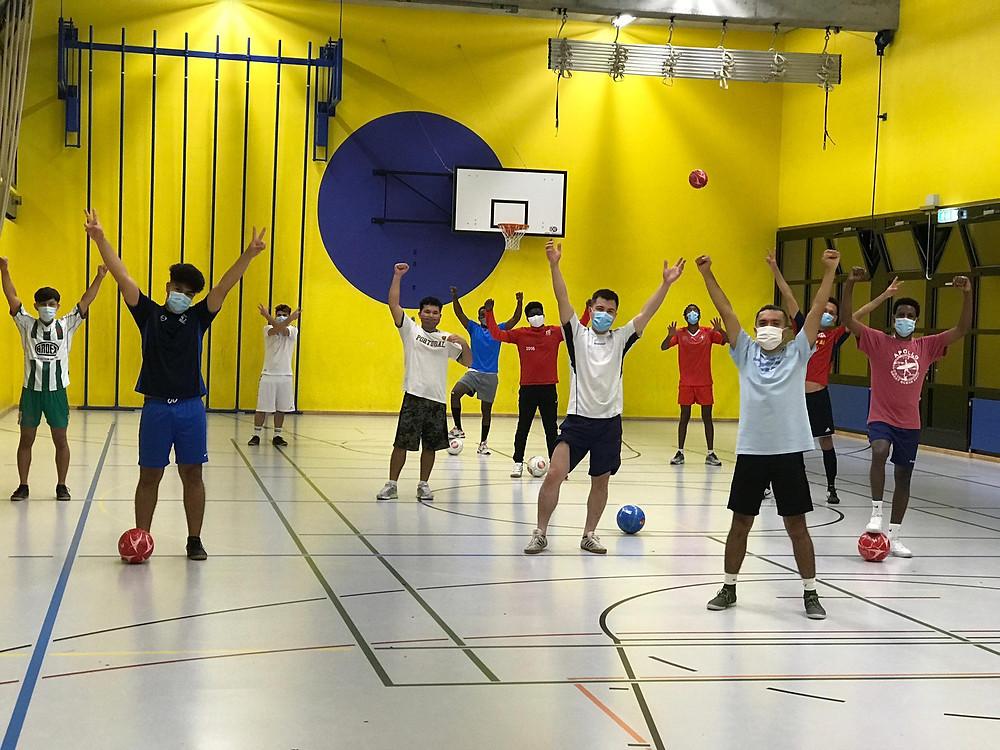 11 Menschen sind in einer Halle und strecken ihre Hände in die Luft. Es wird Fussball gespielt, alle tragen eine Maske.