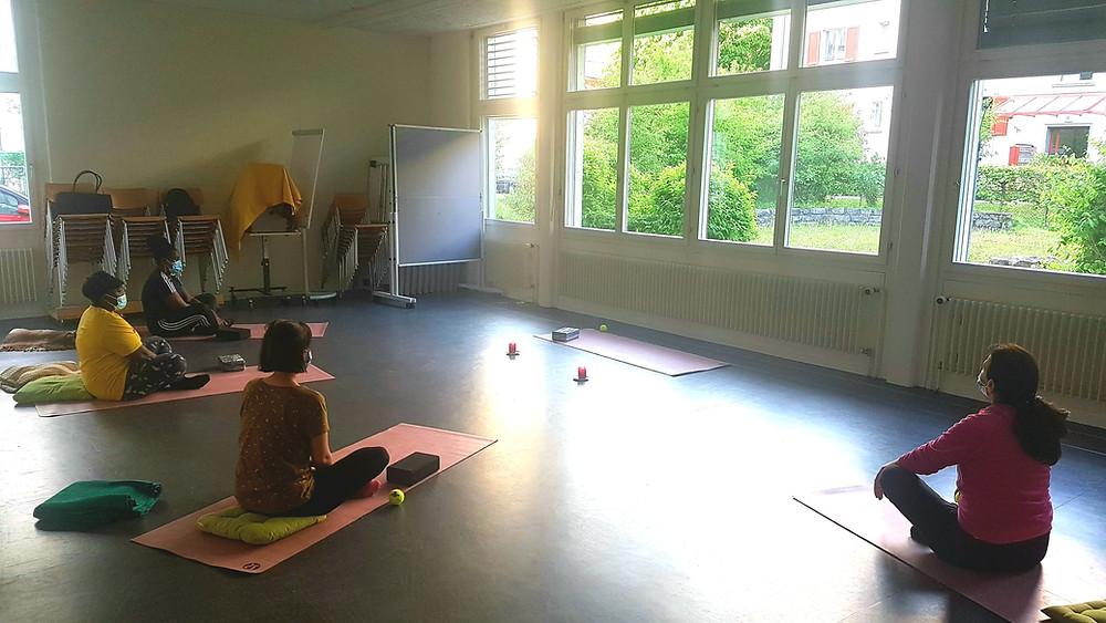 Vier Frauen praktizieren gemeinsam Yoga.