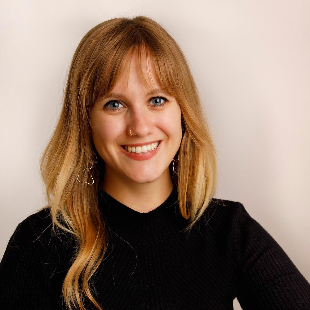 Porträt Eva Gaudenz: 25-jährige Frau mit langem, welligem blondem Haar. Eva trägt einen schwarzen Pulli und goldigen Schmuck. Sie lächelt, man sieht ihre Zähne.