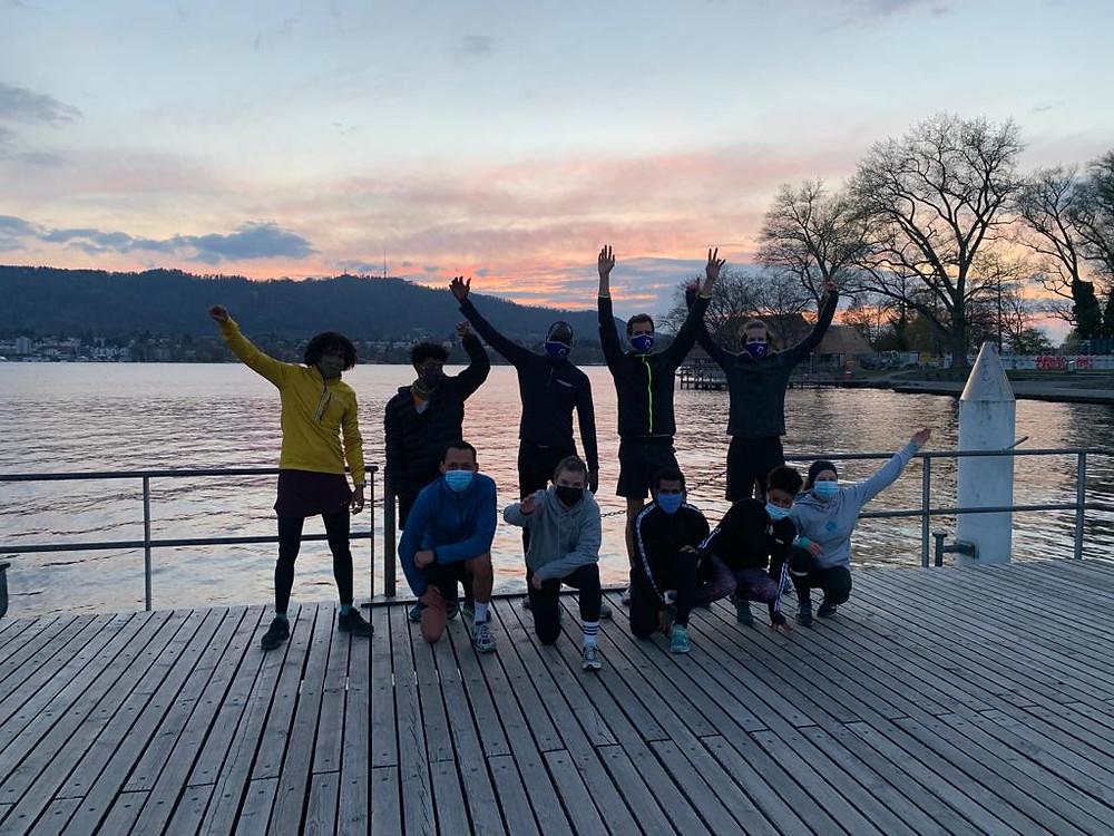 9 Menschen strecken jubelnd ihre Hände in die Luft. Sie sind bei einem Lauf, ein Sonnenuntergang ist ersichtlich.