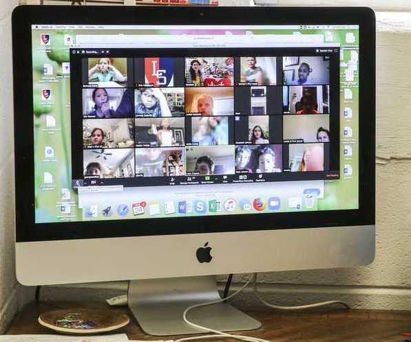 Ein Computer wird fotografiert. Darauf findet gerade ein Zoom Meeting statt. Mehrere Personen unterhalten sich so während des ersten Corona Lockdowns.