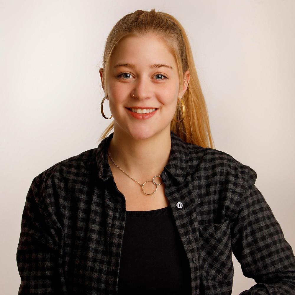 Porträt Milena Bärtschi: 25-jährige Frau mit blondem Zopf. Milena trägt ein grünes Caro-Hemd und goldigen Schmuck.