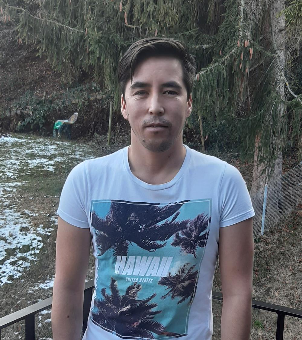 Portrait Gholam Jafari. Gholam steht im Wald und lächelt. Er trägt ein weisses Tshirt, das mit Hawaii beruckt ist.