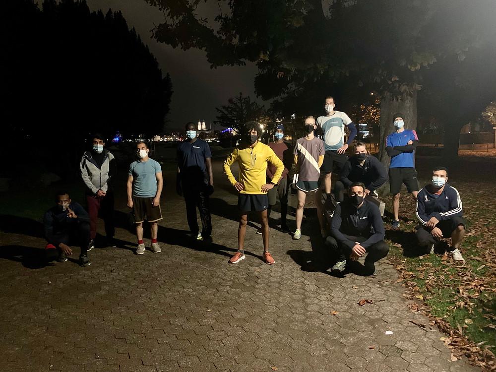 Foto nach dem Lauf Training von Sportegration. 12 Menschen posieren mit Maske und Laufausrüstung. Es ist bereits dunkel.