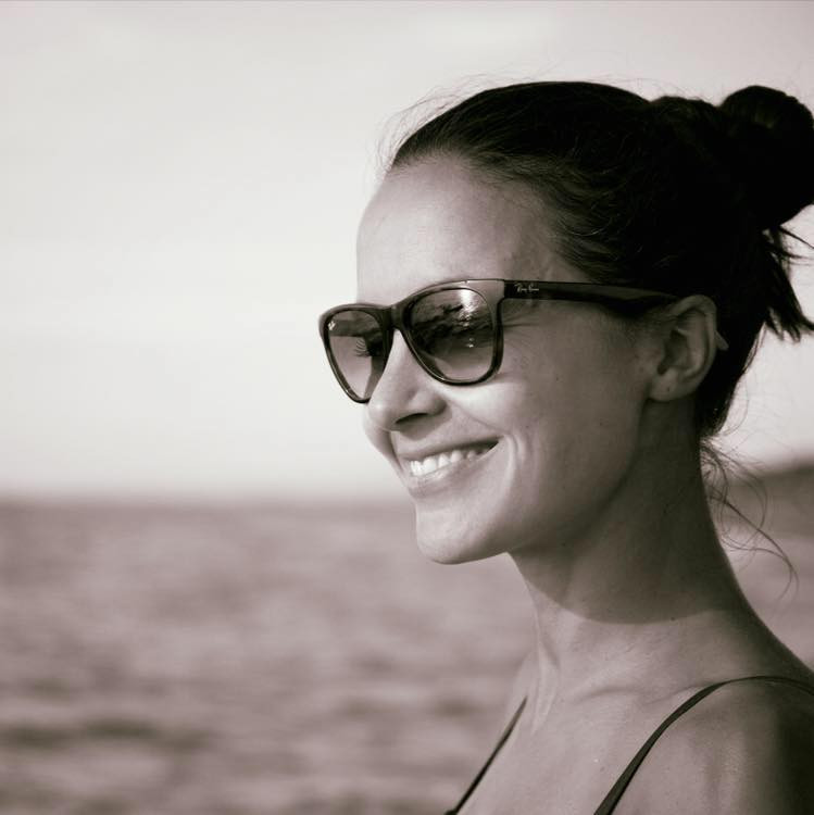 Schwarzweiss Porträt Annina Largo. Sie hat ihre dunkelbraunen Haare zusammengebunden und trägt eine Sonnenbrille. Lächelnd blickt sie in die Ferne. Sie scheint am Meer zu sein.
