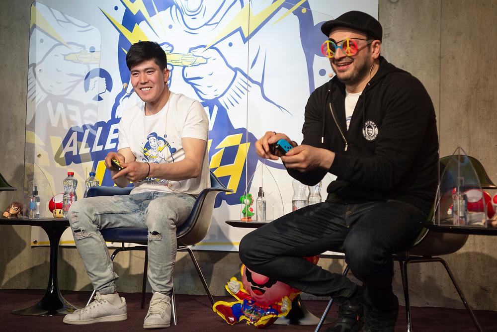 Zwei Männer spielen Mario-Party. Kaya Yanar ist einer von ihnen. Er trägt eine lustige Brille, die ihn am Gewinnen hindert.
