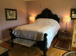 stained glass bedroom with a queen size bed and a baby crib