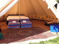 inside a bell tent for glamping with bed and bunting