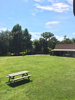 view over swattesfield campsite in suffolk with sunny blue skies