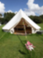 a bell tent for glamping with a windmill outside