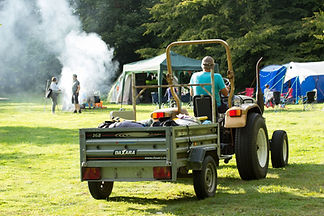 a tractor delivering campers their camping equipment