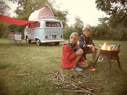 children cooking marshmallows on a fire in front of a VW camper-van at swattesfield campsite