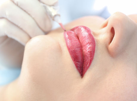 Young beautiful woman making permanent makeup in cosmetology salon.jpg