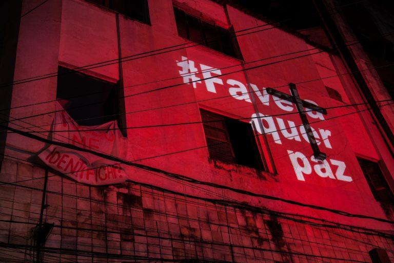 """#PraCegoVer [FOTOGRAFIA]: Foto com tom avermelhado de uma parede. O lado esquerdo tem 4 janelas, na janela do canto inferior esquerdo há um cartaz com a frase """"posso me identificar?"""" . Ao lado da última janela, no canto inferior direito há a mensagem projetada """"#FavelaQuerPaz"""" em letras garrafais brancas que se sobrepõe à uma cruz pregada. Fonte: Cleber Araujo e Cia. Semearte."""