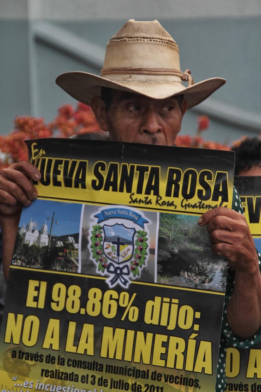 """Legenda: """"98,86% disse NÃO À MINERAÇÃO"""" em consulta comunitária realizada no departamento de Santa Rosa, Guatemala. Fonte: EJ Atlas #Pracegover [Fotografia]: Homem de chapéu de couro marrom claro, pele morena e camisa azul com bolinhas brancas segura uma placa com as duas mãos, cobrindo sua boca. Nela está escrito em espanhol com letras amarelas e pretas """"Em Nueva Santa Rosa, Santa Rosa, Guatemala, 98,86 % disse não à mineração através da consulta municipal de vizinhos realizada em 3 de julho de 2011""""."""