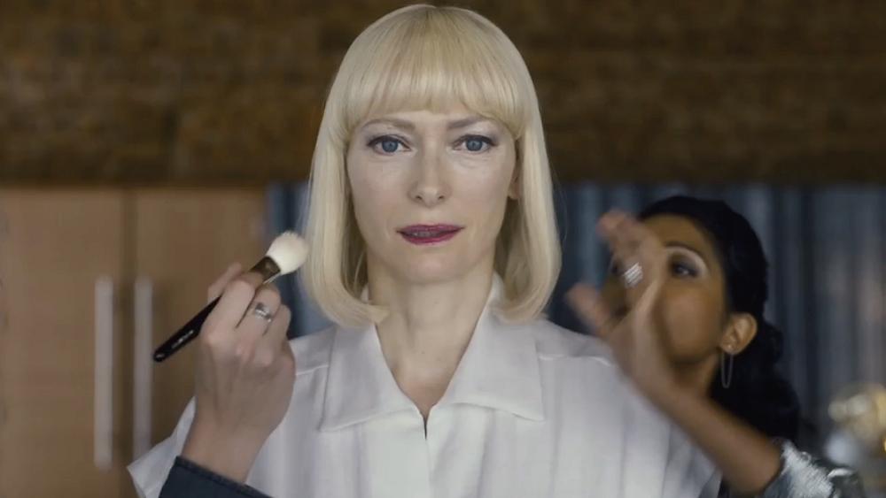 #PraCegoVer [FOTOGRAFIA]: No centro da imagem, Tilda Swinton, que interpreta a personagem Lucy Mirando, está olhando diretamente para a câmera. Uma mão à esquerda, perto do seu rosto, está indo maquiá-la, enquanto uma mulher atrás, à direita, ajeita seu cabelo. Fonte: https://www.comunidadeculturaearte.com/tilda-swinton-a-netflix-foi-o-unico-estudio-que-aprovou-o-projeto-okja/#.