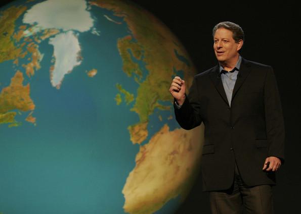 #PraCegoVer [FOTOGRAFIA] Na imagem está o ex vice-presidente do EUA, Al Gore, vestindo um terno preto e uma camisa social azul clara, em frente a uma projeção em 3D do planeta terra, com os continentes em verde, as partes com gelo em azul claro e o mar em azul escuro.