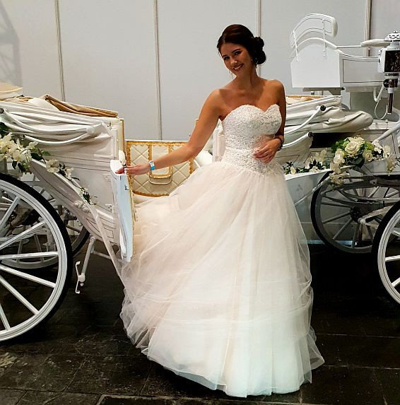 Braut vor weißer Hochzeitskutsche