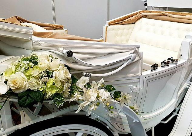 Blumenschmuck an weißer Hochzeitskutsche