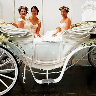 Braut mit Begleitung in einer weißen Hochzeitskutsche