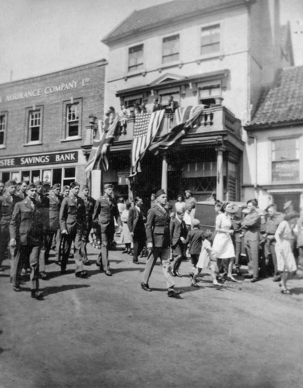 The 100th Bomb Group join a victory parade through the red, white, and blue-strewn streets of Diss