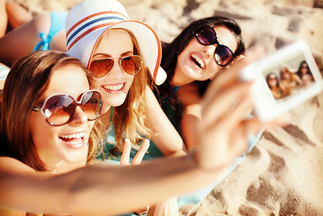 summer holidays, technology and beach concept - girls making self portrait on the beach.jpg