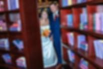 bride and groom peeking through bookcase