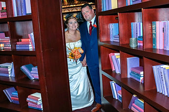 bride and groom peeking through bookcase