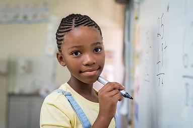 girl-doing-math-at-whiteboard-P3R7GQN (1